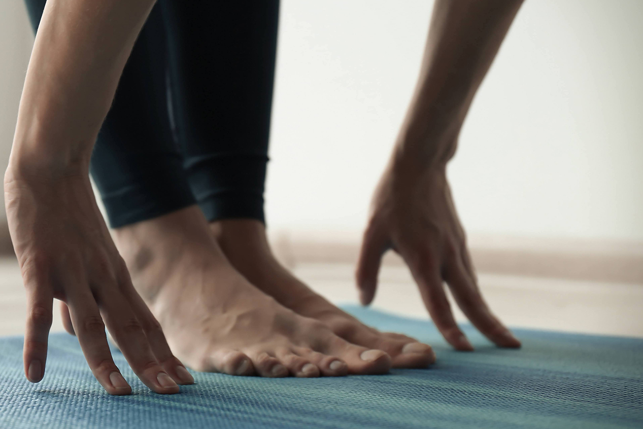 Touching toes on yoga mat. Yoga Therapy, Gillian Motyer.